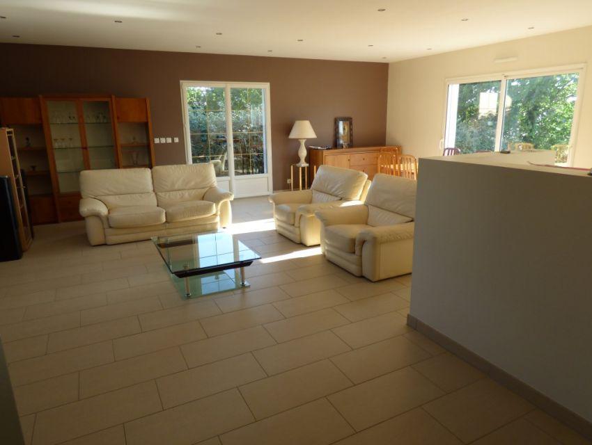 séjour ouvert sur cuisine avec éclairages intégrés et variateur d'intensité lumineuse.