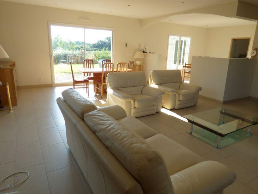 Grand salon/séjour lumineux avec éclairage intégré et larges baies avec ouvertures à galandage.